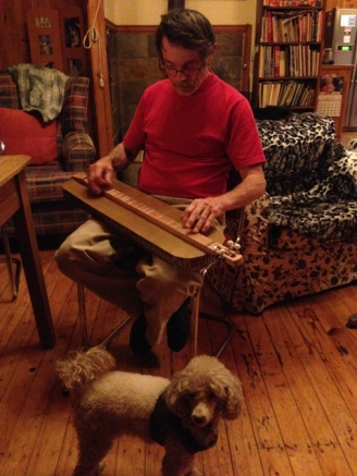 Richard Troughear playing the Ikea cardboard dulcimer that he created.